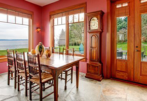 Wooden kitchen table and large wooden grandfather clock in pink painted room